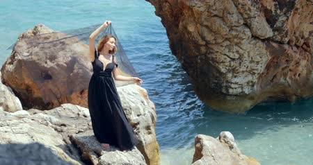 free throw : Beautiful woman standing on rock in elegant black dress and holding black scarf about her head