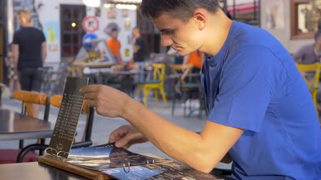 choise : Young man in blue t-shirt reading menu at outdoor cafe Stock Footage
