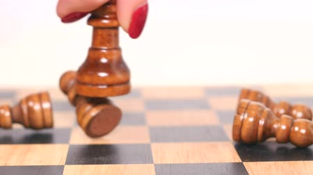 конфронтация : Womans hand holds brown queen figure and takes down brown pawns
