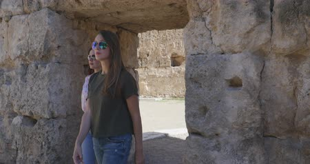 amphitheatre : Young women tourist walking with map in Ancient city Perge with antique colonnada ruins of ancient temple roman architecture on background. This is open air antique historical museum in Turkey Stock Footage