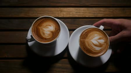 cabeçalho : Male hand bring white cup of coffee with milk heart over wooden background in dark place. Coffee time concept