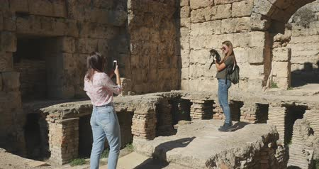 antiquities : Young tourist taking picture in Ancient city Perge with antique colonnada ruins of ancient temple roman architecture on background. This is open air antique historical museum in Turkey Stock Footage