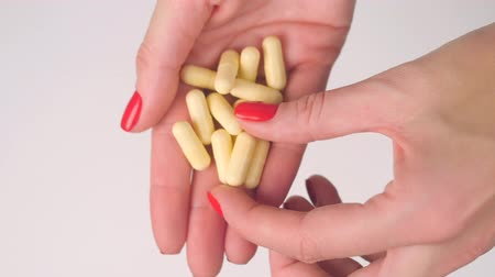 medicals : Womans hand gives yellow capsule pills and takes one with other hand Stock Footage
