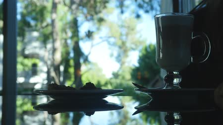 izlenim : Unrecognized woman silhouette  sitting with glass of  cappuccino  and cake in dark place. Window with beautiful forest view on background