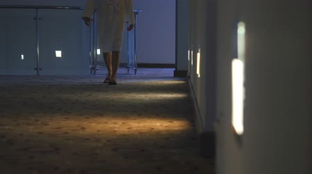 roucho : Unrecognized woman dressed in bathrobe walk in the dark hotel corridor