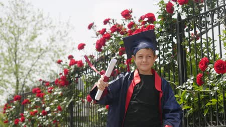 diploma : Happy caucasian child in graduation gown with diploma joyfully dancing near fence full of wild roses. Students celebration graduation, education concept Stockvideo