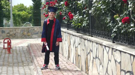 diploma : Happy caucasian child in graduation gown with diploma standing near stone fence full of wild roses. Students celebration graduation, education concept