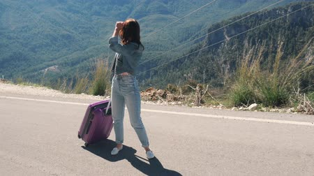 bavul : Beautiful young lady on rural road with suitcase hitchhiking on sunny day outdoors mountains landscape backround Stok Video