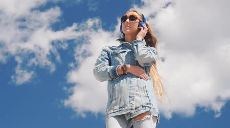 chill out : Young woman in sunglasses and jeans wear listening music with headphones on beautiful blue sky and white clouds background