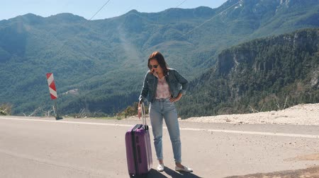 liften : Beautiful young lady on rural road with suitcase hitchhiking on sunny day outdoors stopped to rest, mountains landscape backround Stockvideo
