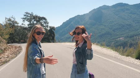 invite : Two young girls tourists in jeans clothes walking down the road with beautiful mountain view, invite to join them