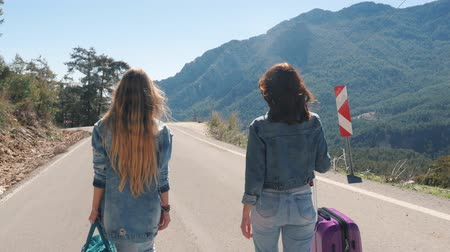 célere : Two young girls tourists in jeans clothes walking down the road with beautiful mountain view