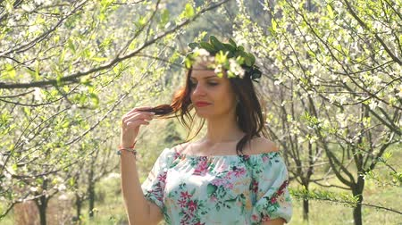 śliwka : Portrait of smiling young beautiful woman with long blond hair in bay leaf wreath in spring blossom plum trees.