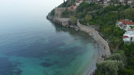 magas szög : Coastal view of ruins of ancient historic castle or fortress on crest of mountain near sea. Beautiful summer tourist landscape in Alanya. Roman Empire ages.