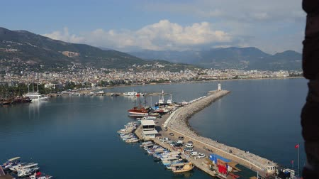 rock wall : View of Alanya harbor with moving cars and people from Alanya Red brig tower. Turkish Riviera Stock Footage