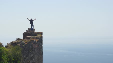 mediaeval : Man tourist staying on the top of ancient castle wall and enjoying the air of freedom. Calm Mediterranean sea on background. Danger action without belay. Stock Footage