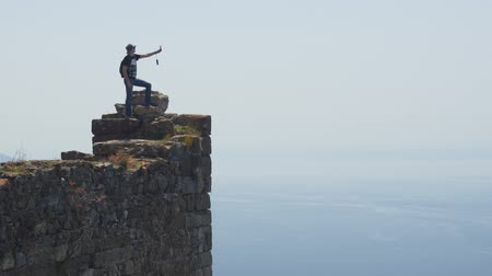 sin fisuras : Man tourist staying on the top of ancient castle wall and shooting video on pocket gimbal camera of calm Mediterranean sea on background. Danger action without belay.
