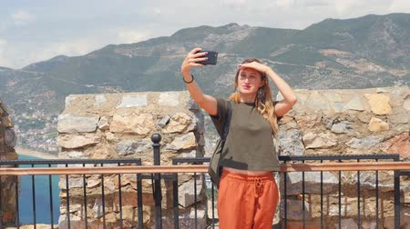 magas szög : Young tourist woman look at ruins and taking pictures and selfie in Alanya peninsula, Antalya district, Turkey, Asia. Famous tourist destination with high mountains. Stock mozgókép