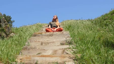 ırklararası : Young caucasian woman with long blond hair sitting on the wooden stair and enjoying sunshine with green grass and blue sky on background. Success life concept