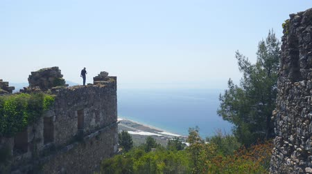 mediaeval : Man tourist walking on ancient castle wall and shooting video on camera with calm Mediterranean sea on background. Danger place without belay.