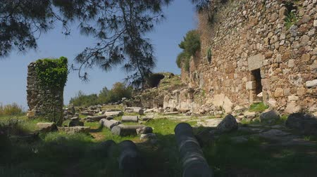 sin fisuras : Walking on ancient greek column ruins with castle wall on background. Calm place without tourists to feel spririt of ages. Archivo de Video