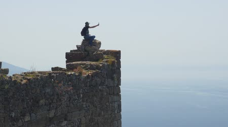 tutmak : Man tourist sitting on the top of ancient castle wall and shooting video on pocket gimbal camera of calm Mediterranean sea on background. Danger action without belay.