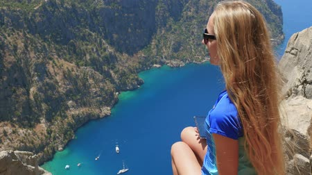 fethiye : Young woman traveler with blond hair and sunglasses enjoying beautiful view of The Butterfly Valley from the top of the mountain, The Butterfly Valley in the city of OludenizFethiye in western Turkey
