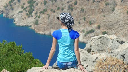 fethiye : Young woman traveller enjoying freedom sitting on the top of the mountain with beatiful viewn of The Butterfly Valley (kelebekler vadisi) in the city of OludenizFethiye, western Turkey.