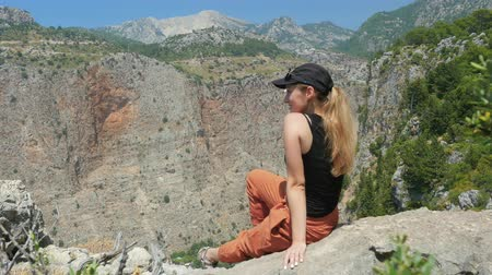 fethiye : Young woman traveler with blond hair and sunglasses enjoying beautiful view of The Butterfly Valley from the top of the mountain. The Butterfly Valley in the city of OludenizFethiye in western Turkey