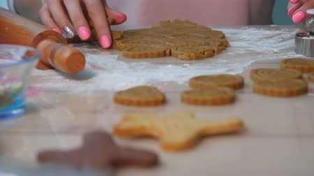 kardámom : Young woman rolling out tasty homemade Christmas cookie dough. Traditional homemade Christmas dessert. Close-up of gingerbread dough with flour and cookie Stock mozgókép