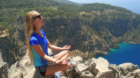 gezgin : Young woman enjoying freedom and taking sun bath with beatiful viewn of Butterfly Valley on background in Turkey Stok Video