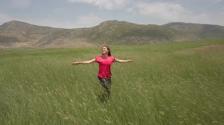 明るく照らされた : A young woman in red t-shirt happily dancing in the green field and touching barley ears. Enjoy agriculture harvest.