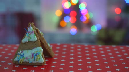 receita : Hand-made eatable gingerbread house on the table, snow decoration, garland background illumination on the Christmas tree