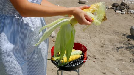 agrarian : Young woman in light blue dress with beautiful manicure cleaning ear of corn to grill it on metal blazer Stock Footage