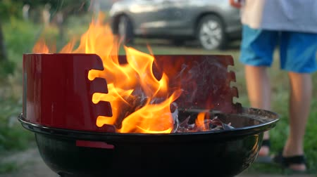 ontvlambaar : Shaking fire wood charcoal for barbecue, orange fire in metal grill brazier. Preparation for summer BBQ party. Summer chill concept