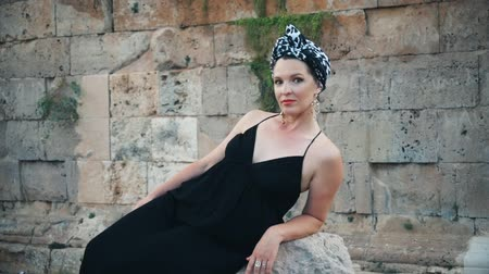 hayran olmak : Beautiful young attractive Muslim woman in long black dress and headscarf (turban) standing on the corner of Hidirlik tower old Roman Empire tower in Antalya, Turkey Stok Video