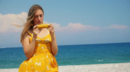 výrazy : Beautiful young woman in yellow summer dress smile and eat corn on the beach in windy weather. The horizon is littered. Blue sea and sky on background