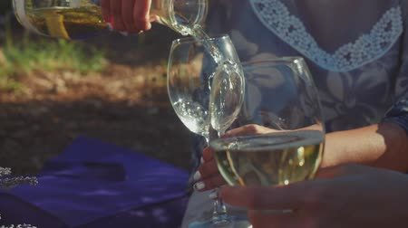 şarap kadehi : Woman pouring white wine into friends glasses outdoors in slow motion. Picnic in lavender fields. Summer concept.