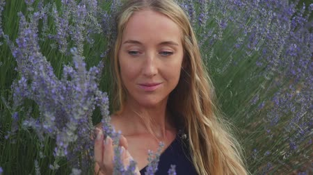 аромат : Beautiful girl is sitting in the middle of field of blossoming lavender, enjoying nature, smells flowers.
