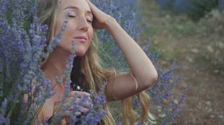vůně : Beautiful girl is sitting with closed eyes in the middle of field of blossoming lavender, enjoying nature.