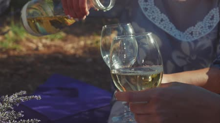 összejövetel : Woman pouring white wine into friends glasses outdoors. Picnic in lavender fields. Summer concept.