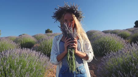 gözlü : Young woman in wreath enjoying fragrant of lavender bouquet standing in lavender field in windy weather. Slow motion. Stok Video