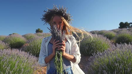 изобилие : Young woman in wreath enjoying fragrant of lavender bouquet standing in lavender field in windy weather. Slow motion. Стоковые видеозаписи