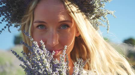 gözlü : Portrait of young woman in wreath enjoying fragrant of lavender bouquet standing in lavender field in windy weather. Slow motion Stok Video