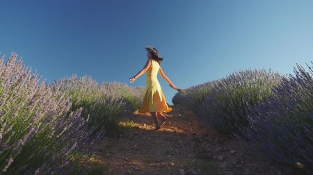 fondness : Young woman in yellow dress and in wreath dancing in lavender field. Slow motion