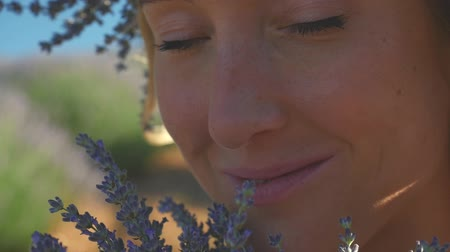 gözlü : Extreme closeup of young woman in wreath enjoying fragrant of lavender bouquet standing in lavender field in windy weather. Stok Video
