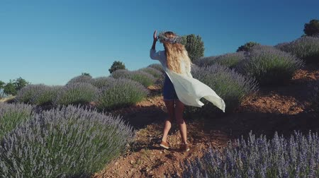 szag : Young woman in yellow dress and in wreath dancing in lavender field. Slow motion