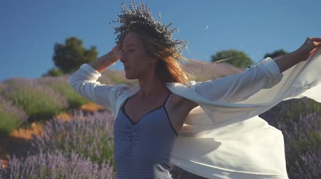 lavender field : Young woman in lavender wreath standing gorgeously in lavender field in windy weather. Long shirt waving in slow motion