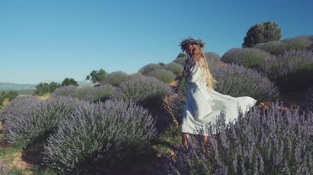 изобилие : Young woman in casual clothes wearing wreath walking happily in lavender field.