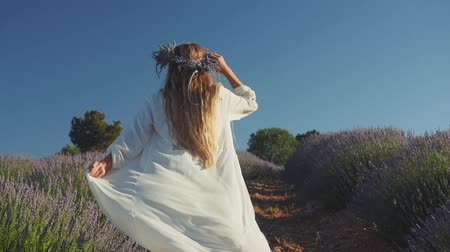 изобилие : Young woman in casual clothes wearing wreath happily running in lavender field. Slow motion Стоковые видеозаписи